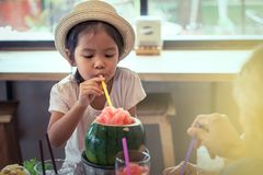 Cute asian little girl is drinking watermelon blended juice Stock Images