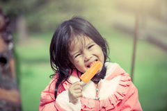 Cute asian little girl is eating ice-cream in the park Royalty Free Stock Images