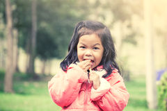 Cute asian little girl is eating ice-cream in the park Stock Photos