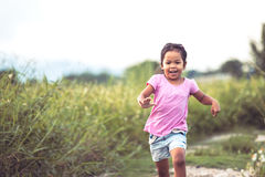 Cute asian little girl having fun and running in the park Stock Photo