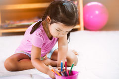 Cute asian little girl having fun to paint with crayon Stock Photography