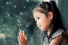 Cute asian little girl looking outside through the window Stock Photography