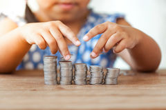 Cute asian little girl playing with coins making stacks of money Royalty Free Stock Images
