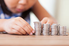 Cute asian little girl playing with coins making stacks of money. Kid saving money for the future concept Royalty Free Stock Image