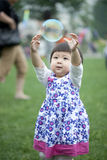Cute asian little girl plays with a giant bubble Stock Photography