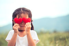 Cute asian little girl with red hearts on the eyes. In vintage color tone Royalty Free Stock Photos