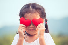 Cute asian little girl with red hearts on the eyes. In vintage color tone Royalty Free Stock Photography