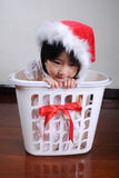 Cute asian little girl in a santa hat sitting in gift basket Royalty Free Stock Photo