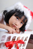 Cute asian little girl in a santa hat sitting in gift basket Royalty Free Stock Image