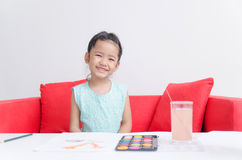 Cute asian little girl smile and play water color. At home Stock Images