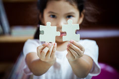 Cute asian little girl is trying to connect couple jigsaw puzzle. Piece to learn to find solution stock images