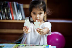 Cute asian little girl is trying to connect couple jigsaw puzzle Royalty Free Stock Photos