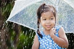 Cute asian little girl with umbrella in rain. Portrait of cute asian little girl with umbrella in rain Stock Photography