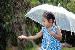 Cute asian little girl with umbrella in rain. Portrait of cute asian little girl with umbrella in rain Stock Photos