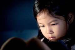 Cute asian little girl using digital tablet at night. In the bedroom in dark blue color tone stock photos