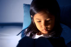 Cute asian little girl using digital tablet at night. In the bedroom in dark blue color tone royalty free stock image