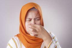 Cute Asian Muslim Lady Close Her Nose royalty free stock photos