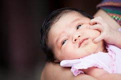 Cute asian newborn baby girl resting on mother`s arm Royalty Free Stock Photography