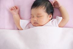 Cute asian newborn baby girl sleeping in bed Stock Photography