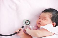 Cute asian newborn baby girl sleeping and holding stethoscope Stock Photography