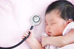 Cute asian newborn baby girl sleeping and holding stethoscope stock images
