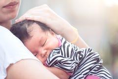Cute asian newborn baby girl sleeping on mother`s chest Stock Photos