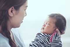 Cute asian newborn baby girl sleeping on mother`s hand. Stock Photography