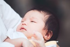 Cute asian newborn baby girl sleeping on mother`s shoulder Stock Photography