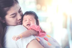 Cute asian newborn baby girl sleeping on mother`s shoulder. Stock Photography