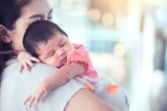 Cute asian newborn baby girl sleeping on mother`s shoulder Royalty Free Stock Photos