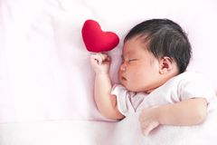 Cute asian newborn baby girl sleeping with red heart Royalty Free Stock Images