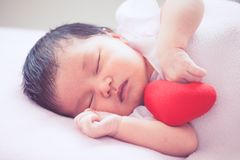 Cute asian newborn baby girl sleeping with red heart Royalty Free Stock Photography