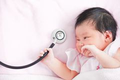 Cute asian newborn baby girl smiling and holding stethoscope. Cute asian newborn baby girl smiling and holding medical stethoscope in hand stock photos