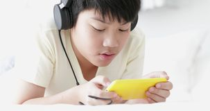Cute asian preteen boy ware headphone and using smart phone with his sister. Doing hand craft background stock footage