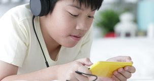 Cute asian preteen boy ware headphone and using smart phone with his sister. Doing hand craft background stock video