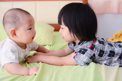 Cute Asian sisters playing on bed. Royalty Free Stock Photography