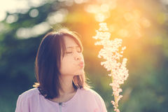 Cute Asian teenager girl blower grass flower with sun light. Royalty Free Stock Images