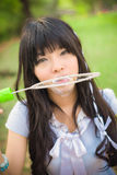 Cute Asian Thai girl is blowing a big soap bubble.  Focus on the Royalty Free Stock Photos