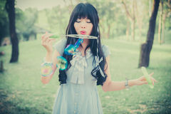 Cute Asian Thai girl is blowing a soap bubbles in the park in dr stock photography