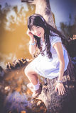 A cute Asian Thai girl is sitting on a riverside tree trunk Royalty Free Stock Photo