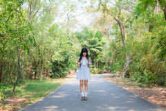 A cute Asian Thai girl is standing on a forest path alone stock image