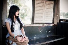 Cute Asian Thai girl in vintage clothes is waiting alone royalty free stock image