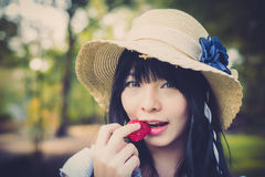 A cute Asian Thai girl with vintage clothing is biting strawber Stock Photo
