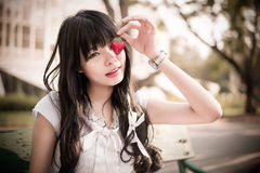 A cute Asian Thai girl with vintage clothing is picking a straw royalty free stock photo