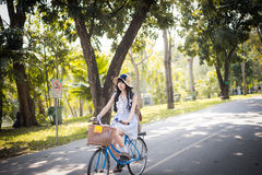 Cute Asian Thai girl in vintage clothing is riding a bicycle in the sunny summer park Royalty Free Stock Images