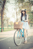 Cute Asian Thai girl in vintage clothing is standing with her bi Stock Image
