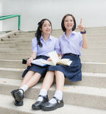 Cute Asian Thai high schoolgirls student couple pointing royalty free stock images