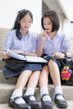 Cute Asian Thai high schoolgirls student couple reading in school Royalty Free Stock Photo