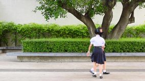 Cute Asian Thai high schoolgirls student couple in school uniform are having fun playing chasing and catching a doll. With her student friend stock video