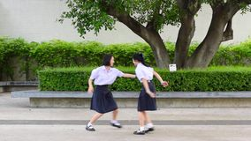 Cute Asian Thai high schoolgirls student couple in school uniform are having fun playing chasing and catching a doll. With her student friend stock video footage